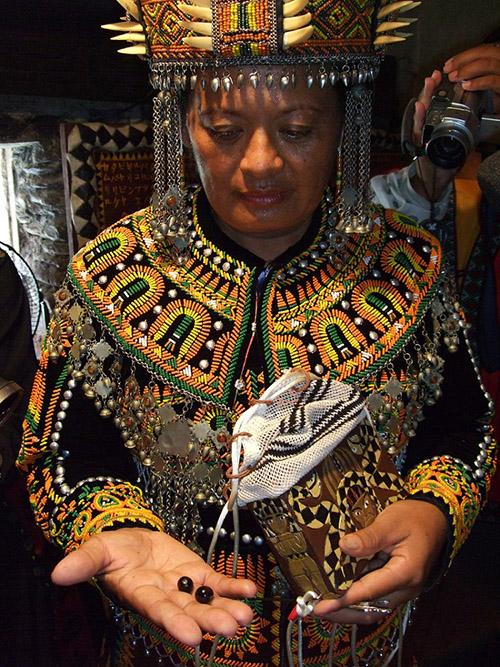 巫珠(圖中右手所示)是排灣族女巫師的必備靈物,代表受到神靈揀選、註定成巫的命運,一般會收藏於巫師箱袋中(圖中左手所持)。圖│胡台麗提供