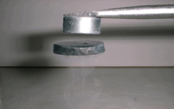 這不是魔法,而是超導體 (Superconductor) 的完全反磁現象。圖中是一高溫超導體懸浮在磁鐵之下。圖│吳茂昆提供