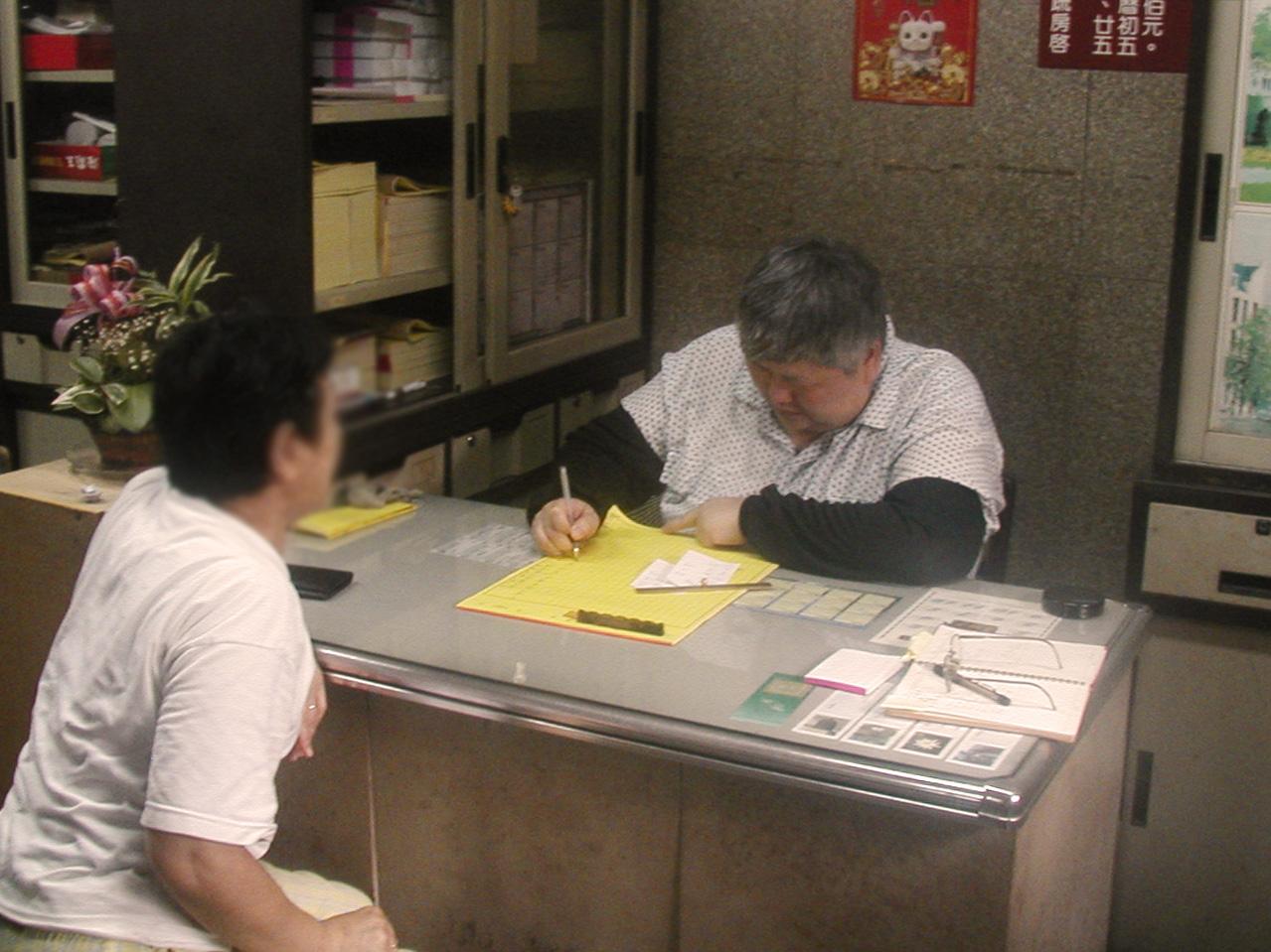 十年前新莊地藏庵只有一位筆生幫忙寫牒文,現在有五位,民眾甚至需要抽號碼牌。圖片來源│康豹提供