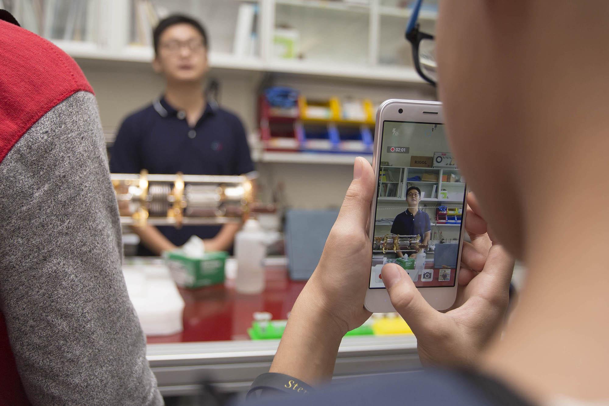 實驗室成員陳則言、邱俊傑,向參訪民眾說明量子電子元件的製程與設備。 圖│研之有物