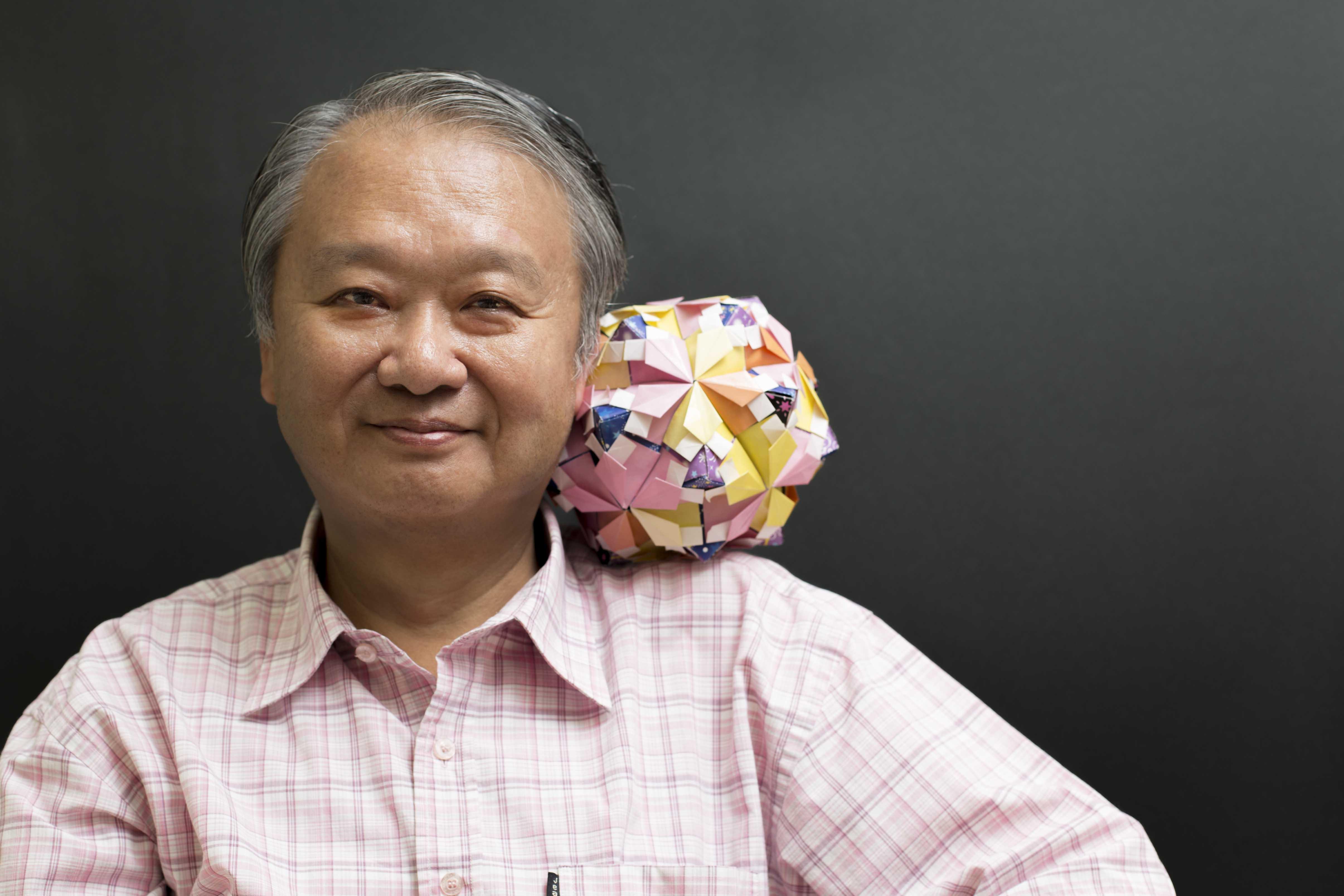李國偉秀出一顆球形的組合摺紙,是女兒先用紙張摺了許多小元件,再將小元件組成球形結構。「這很不簡單,曾經掉到地上散了,只好再請我女兒把它組回來。」 攝影│張語辰