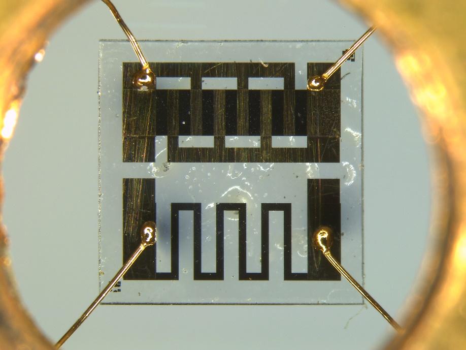 2010 年開發的第五代比熱量測晶片,Ni-Cr 與 RuO2 薄膜由無塵室半導體製程完成。晶片由四條金線懸於真空中,與控溫之銅座相連接。 圖片來源│陳洋元提供