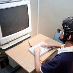 受試者戴著腦波實驗專用帽,看著電腦螢幕按按鍵、或是玩遊戲,藉此收集大腦的反應數據。 圖片來源│大腦與語言實驗室