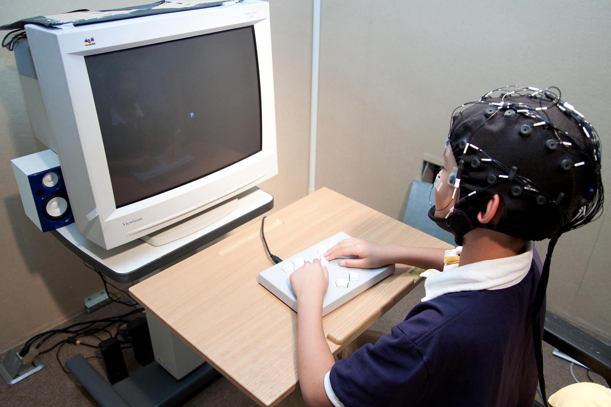 受試者戴著腦波實驗專用帽,看著電腦螢幕按按鍵、或是玩遊戲,藉此收集大腦的反應數據。圖│大腦與語言實驗室