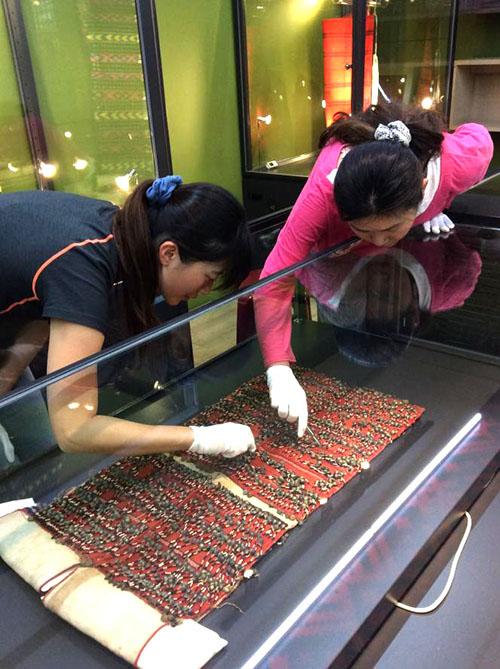 博物館員正在整理貝珠衣上的銅鈴,展期內文物的持拿和翻動必須由隨行館員負責,參觀者不能自行觸碰。圖│中研院民族所(攝影│楊雯娟)