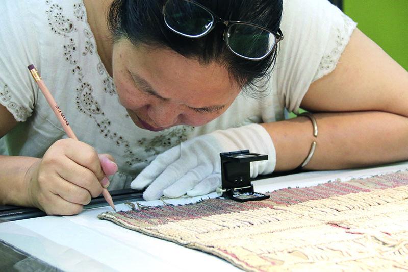 尤瑪正在繪製織品的紋路。本次展示的重點之一,即讓對於傳統技藝有興趣的部落或非部落織者研究老物件的織法。尤瑪事先教大家如何研究紀錄老織品的組織和結構、如何從不同角度照相、繪圖,然後織者在展場工作坊與博物館員共同合作研究老物件。圖│中研院民族所