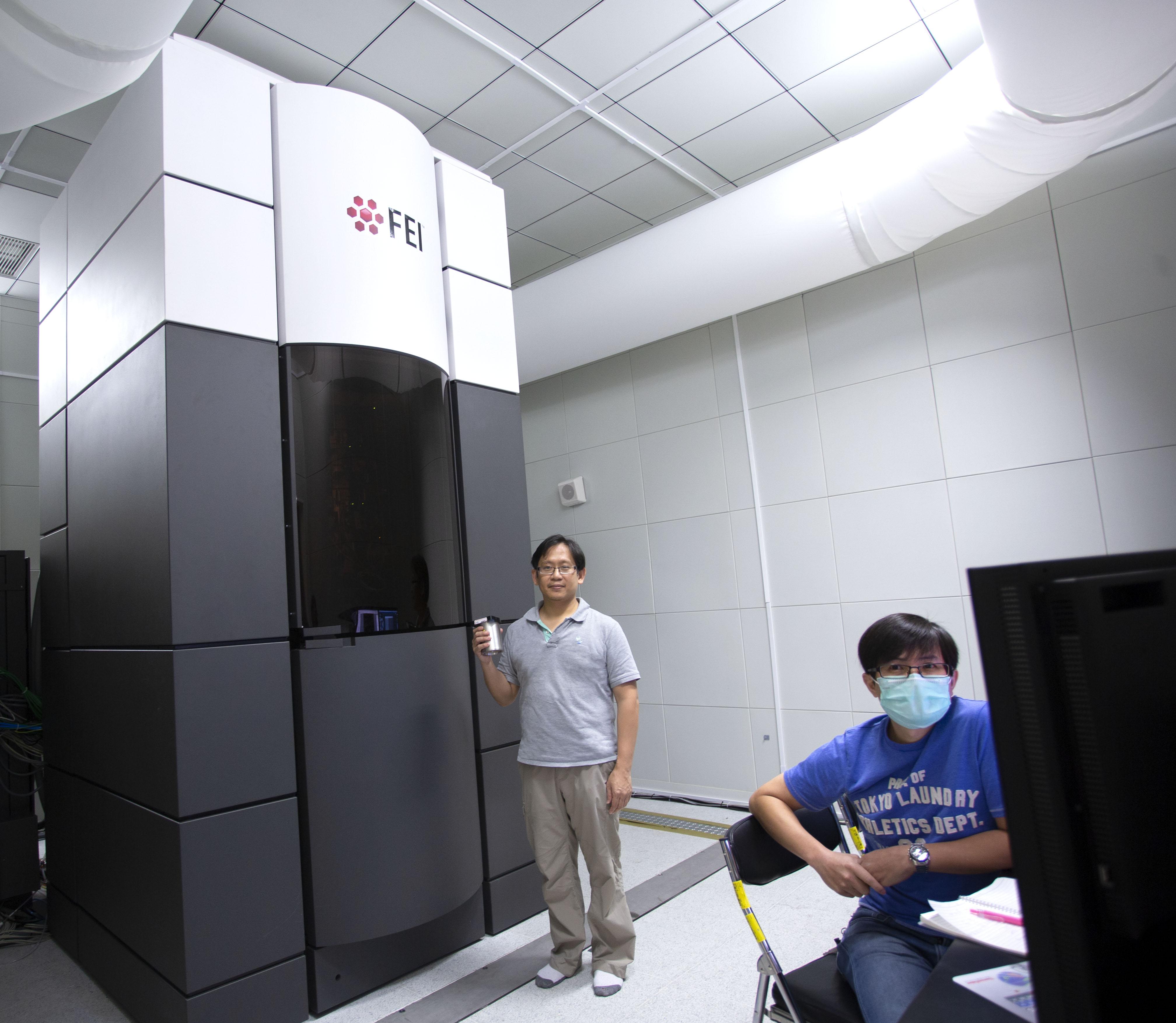 中研院的一台高階冷凍電子顯微鏡:Titan Krios。為了不干擾冷凍電顯的觀測,整個環境設計為防震、吸音、控溫、控濕,一絲絲微風也沒有。圖中立者為中研院生化所副研究員何孟樵, 坐者為冷凍電顯中心經理張淵智。攝影│林洵安