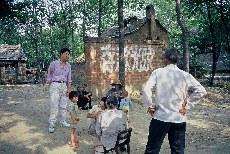 中國鄉村牆上經常可見大幅標語,吳介民笑稱:「你得反著看。」「存款光榮」意指要求「強迫儲蓄」,圖中為典型的農村「留守老人」、「留守兒童」,大量農村青壯人口到沿海工廠打工,村裡就剩下老人、幼兒。圖│吳介民