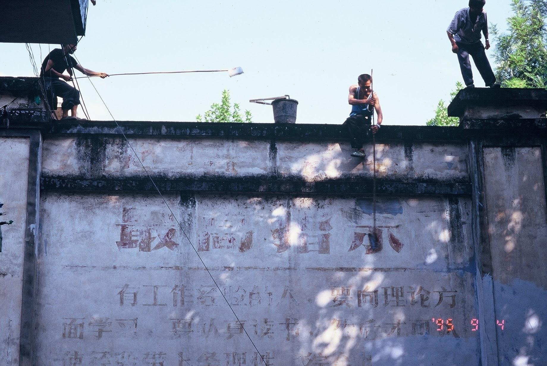 1995 年 9 月 4 日,吳介民與黎安友在四川邊遠小鎮上,目睹工人正用白漆抹去牆上的毛語錄最高指示,彷彿也見到一個時代的消逝終結。圖│吳介民