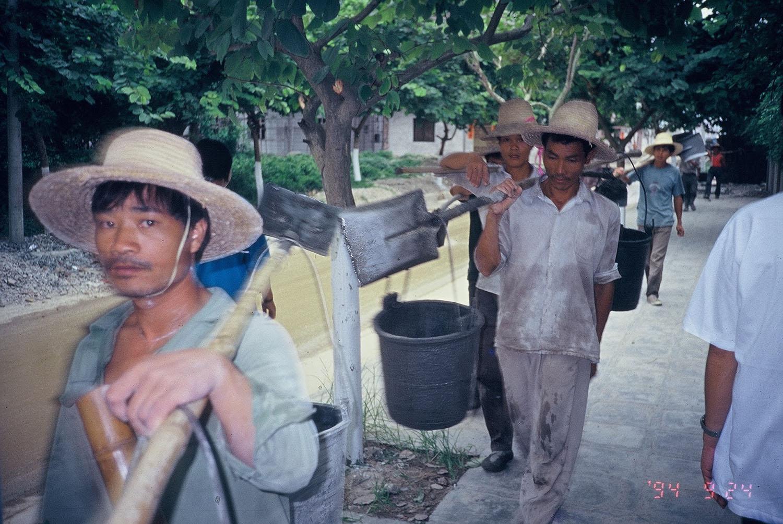 吳介民在廣東村落田調,一群民工從他身前經過,他順手拿起相機,按下快門的剎那,身前的工人正好抬起頭,直直望向鏡頭,留下這張意味深長的照片。民工是過去中國經濟成長的沉默貢獻與犧牲者,建築隊是最底層的民工,經常被拖欠工資、睡在工地。圖│吳介民